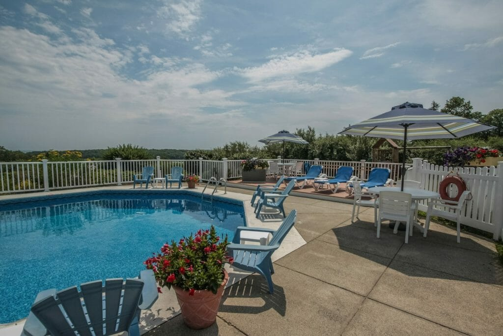 Outdoor Pool in Camden at Glen Cove Inn - pool chairs with an umbrella and planters with a blue sky
